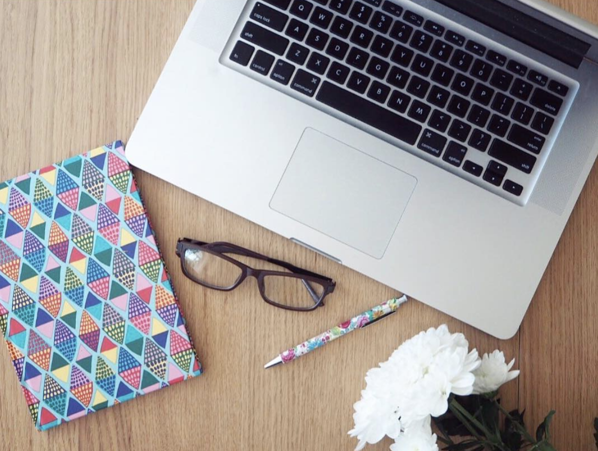 Laptop with notebook and glasses